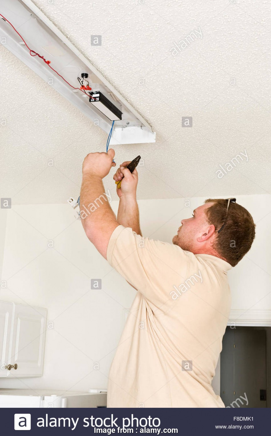install light fixture electrician A Male Electrician Installing a Fluorescent Lighting Fixture Stock 11 Brilliant Install Light Fixture Electrician Solutions