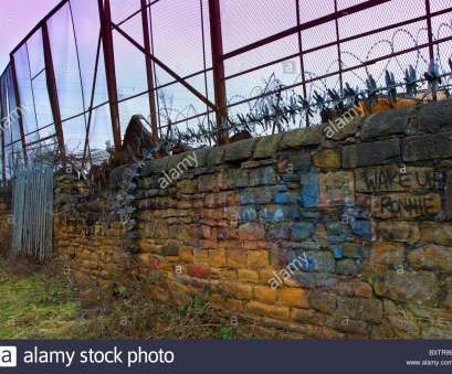 wire mesh fence with stones Old stone wall with high mesh fence together with barbed wire, razor wire, revolving Wire Mesh Fence With Stones New Old Stone Wall With High Mesh Fence Together With Barbed Wire, Razor Wire, Revolving Ideas